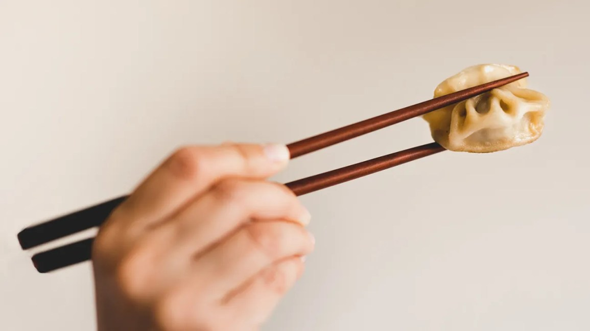 Person eating steamed dumpling with chopsticks
