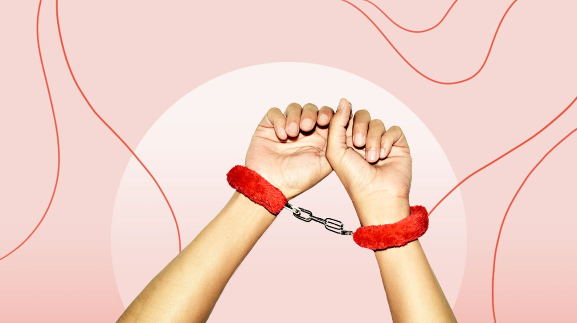 cropped view of a person's wrists encased in red, fuzzy handcuffs against a mauve and light pink color-blocked background