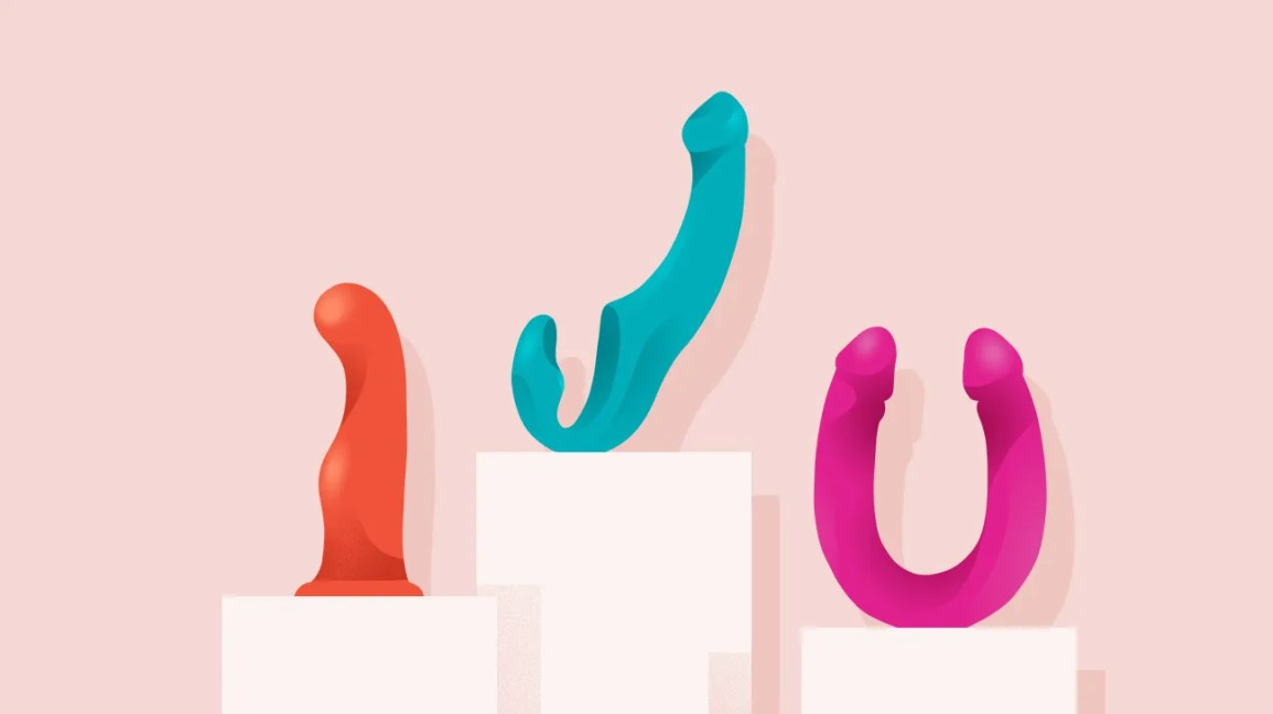 illustration of three dildos — including a red suction dildo, sky blue dildo with an added arm for external clitoral or perineal stimulation, and a hot pink double-ended dildo — set against a muted pink background. each toy is sitting on its own light pink column of varying height.