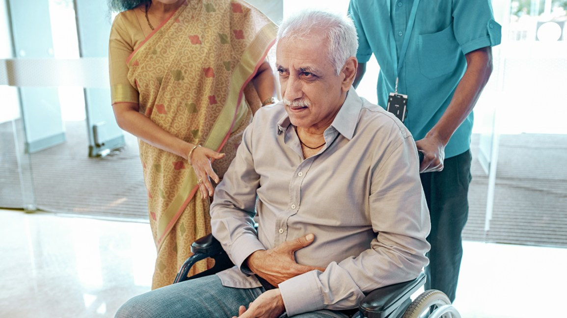 A man sits in a wheelchair with pain radiating to his stomach area.