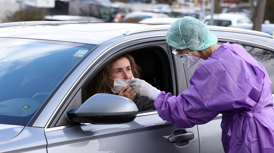 a healthcare worker tests a woman, sitting in her car, for symptoms of the novel coronavirus