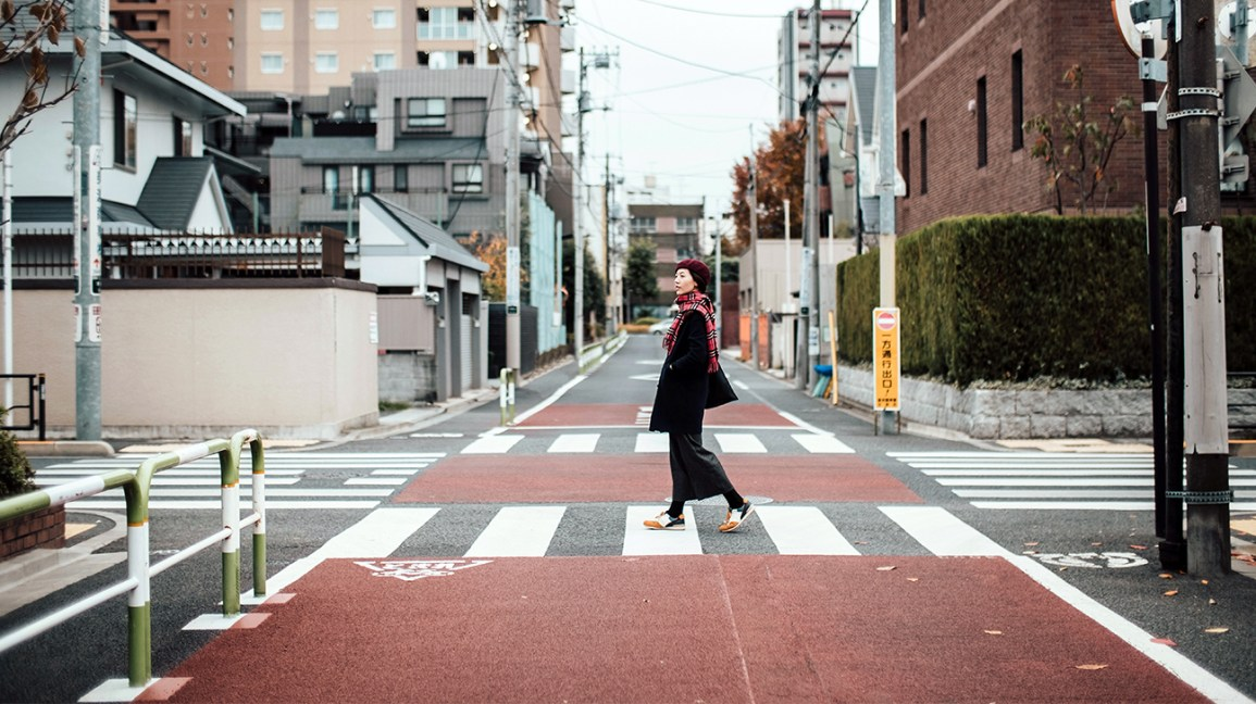 una donna cammina lentamente per le strade della città