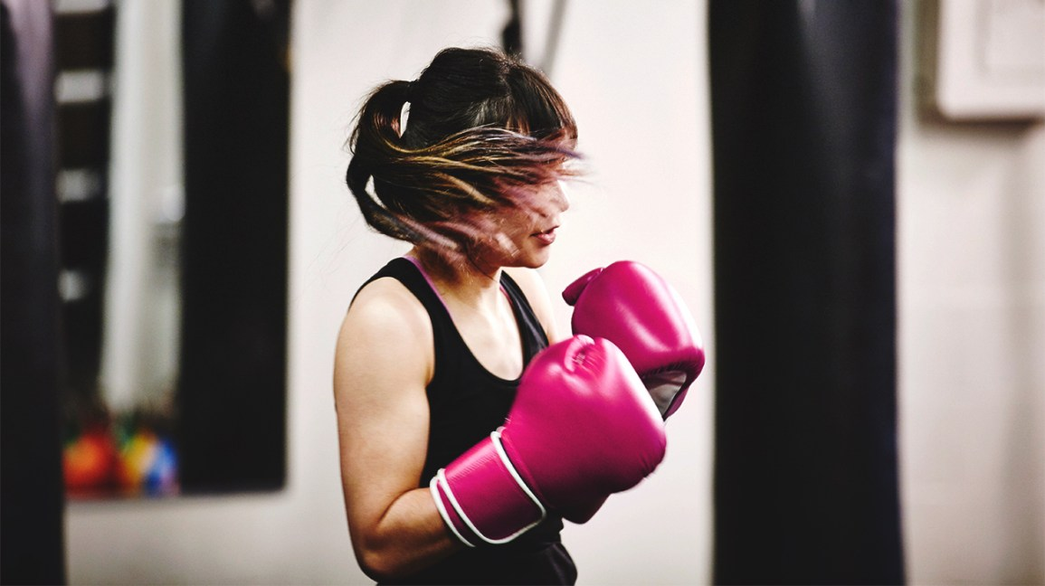 A woman wears boxing gloves in a gym, which could cause a blow or punch to the liver.
