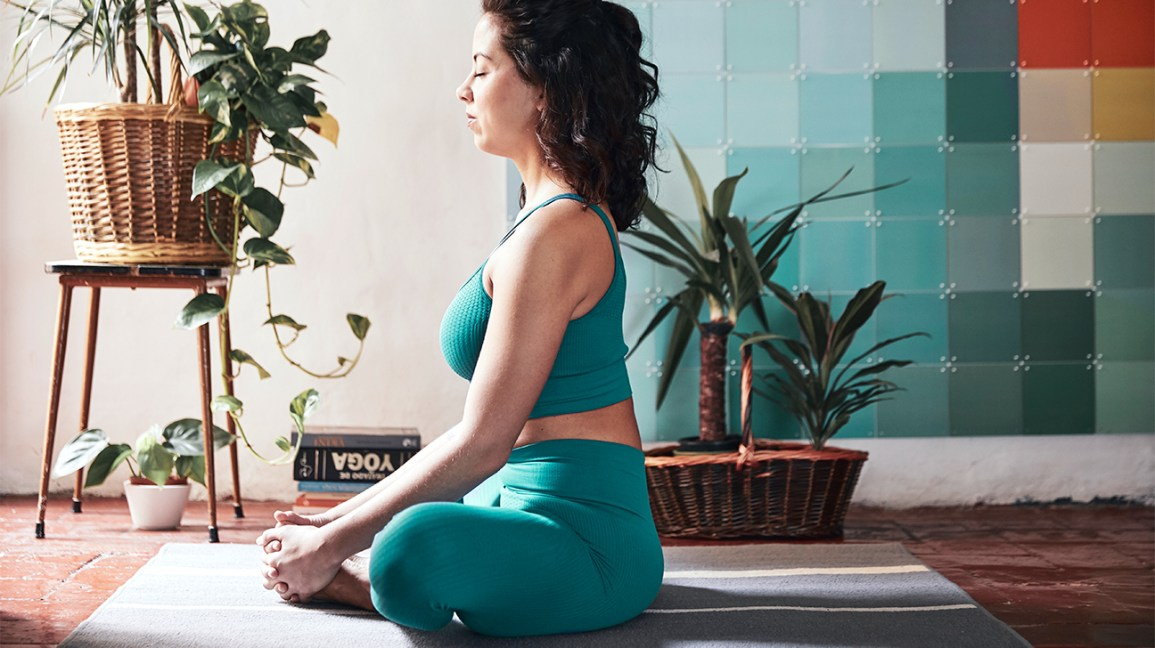 A woman sits in a meditative pose, one of the ways that research shows you can boost your intelligence.