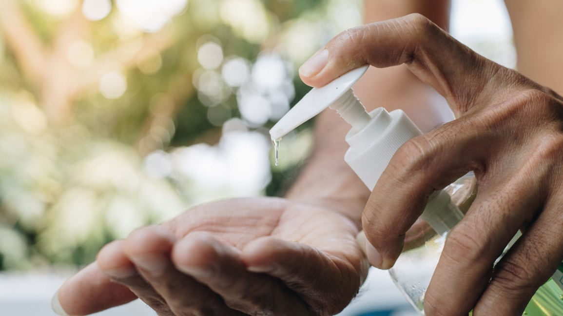 A closeup of a person applying hand sanitizer from a bottle onto the palm of their hands.