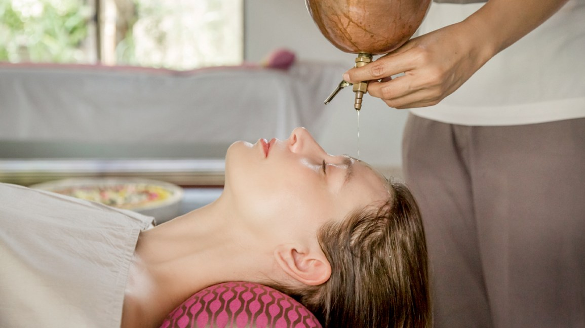 woman having oil poured on forehead for shirodhara treatment