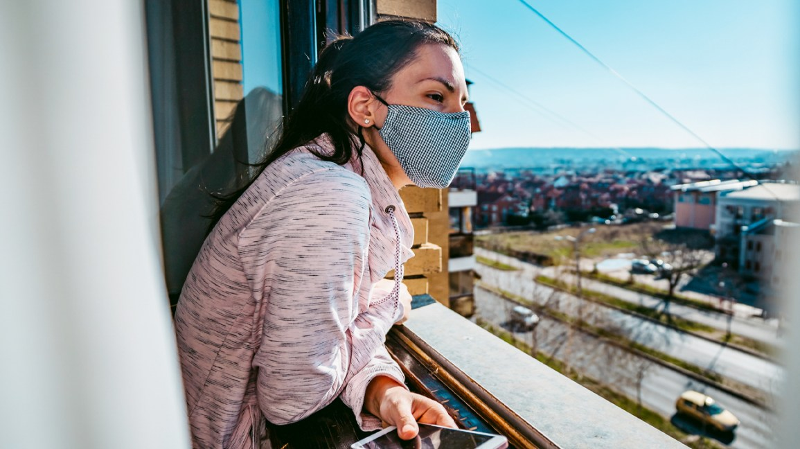 person wearing a cloth face mask and looking out over a balcony