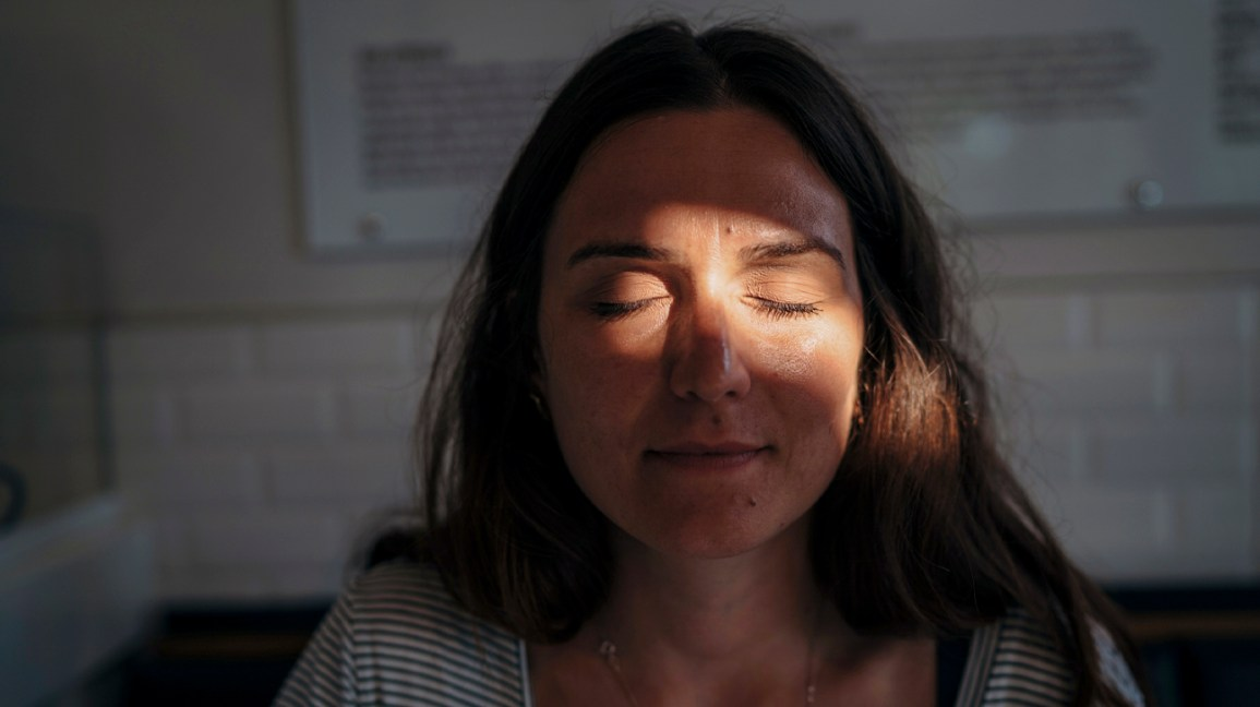 A woman sits in a darkened room with her eyes closed due to a migraine.