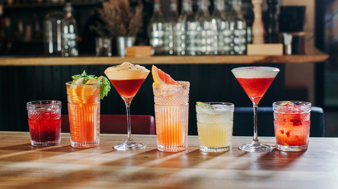 line of mocktails sitting on a bar