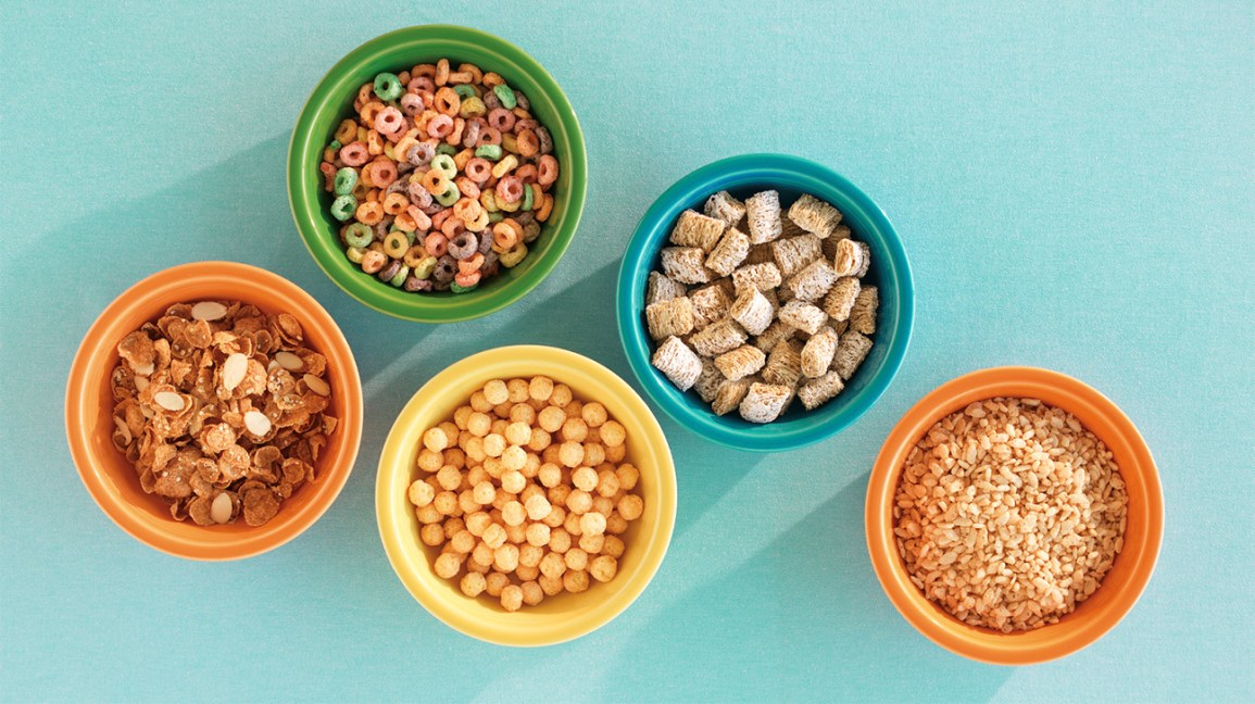 a selection of dry breakfast cereals in colorful bowls