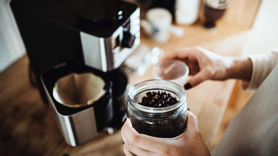 A person preparing coffee beans for a grinder