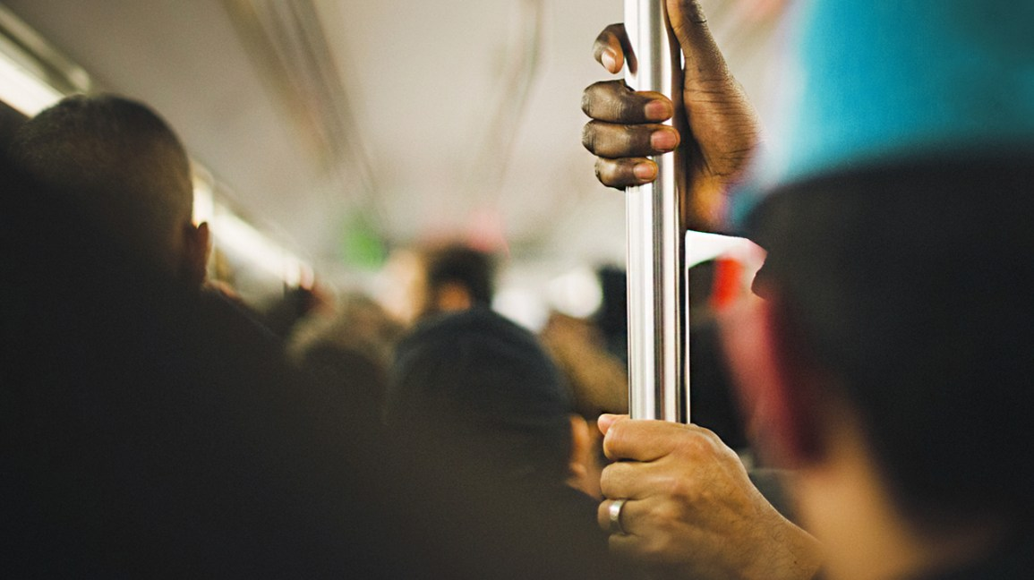 A person holds on to a bar in a crowded train, a potential way that the novel coronavirus can be spread from person to person.