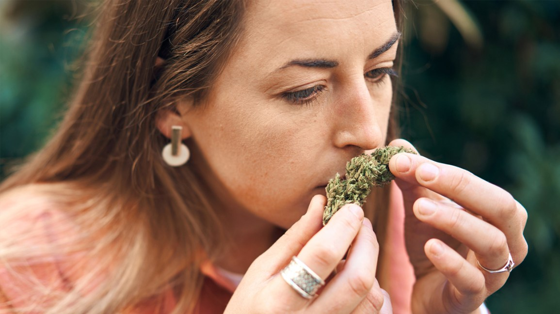 woman holding weed up to her nose and smelling it