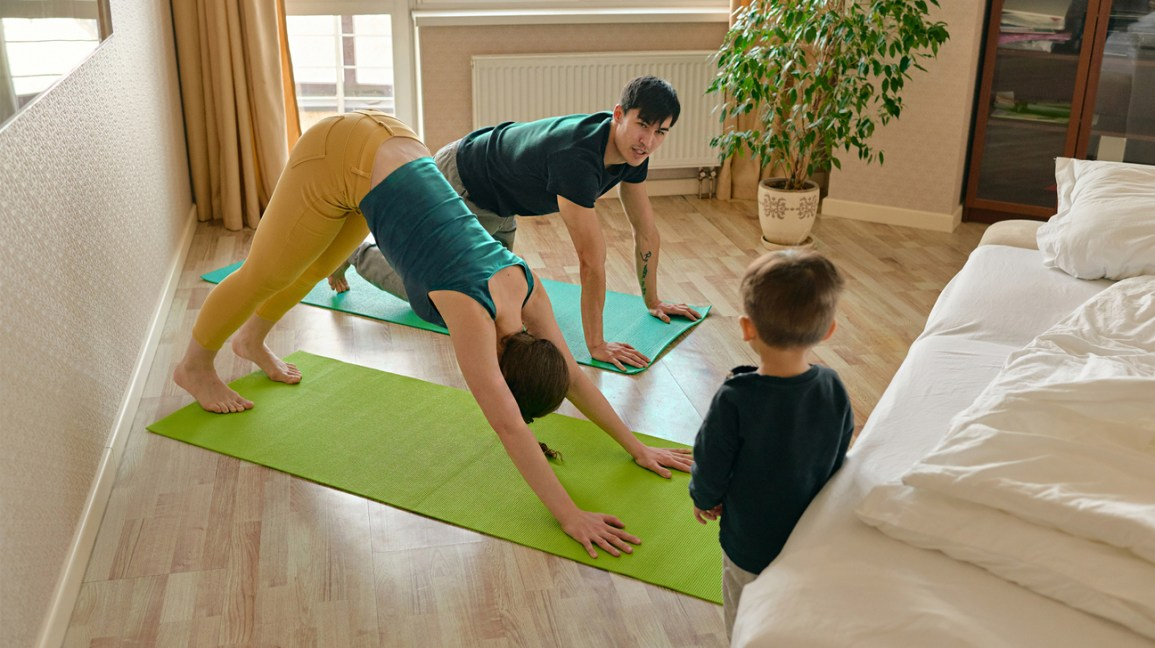 parents do yoga while child watches