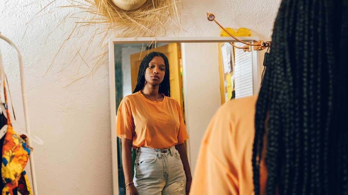 cropped, knees-up view of person wearing a loose, orange tee shirt tucked into high-waisted jeans, looking at their reflection in a full-length mirror