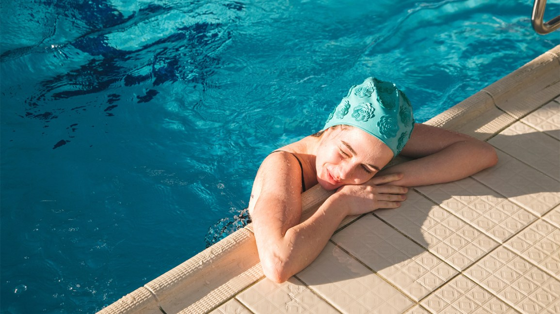 A woman in a swimming pool rests her head and arms on the side of the pool.