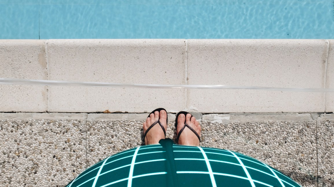 pregnant person stands next to swimming pool