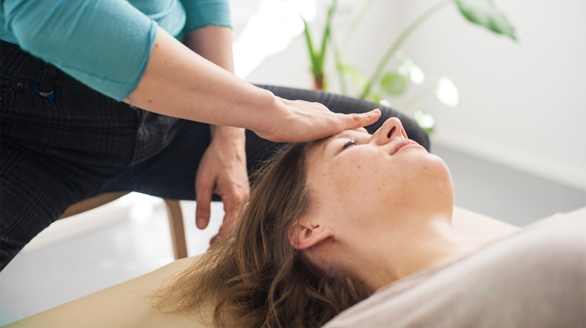 woman laying on table while someone massages her forehead