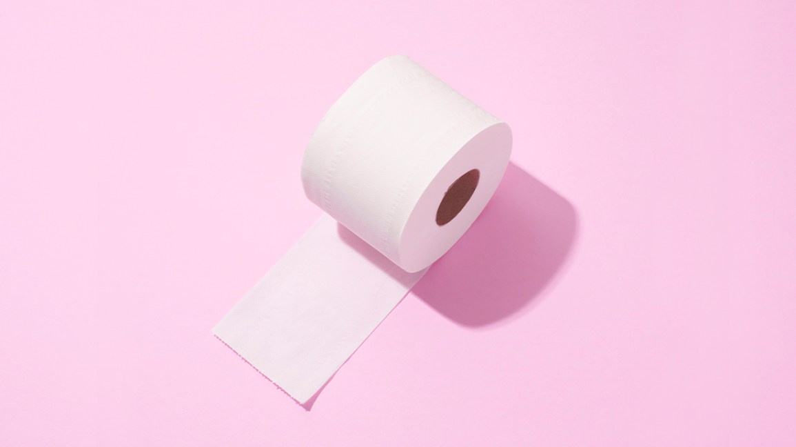 slightly unravelled roll of toilet paper sitting on a light pink background