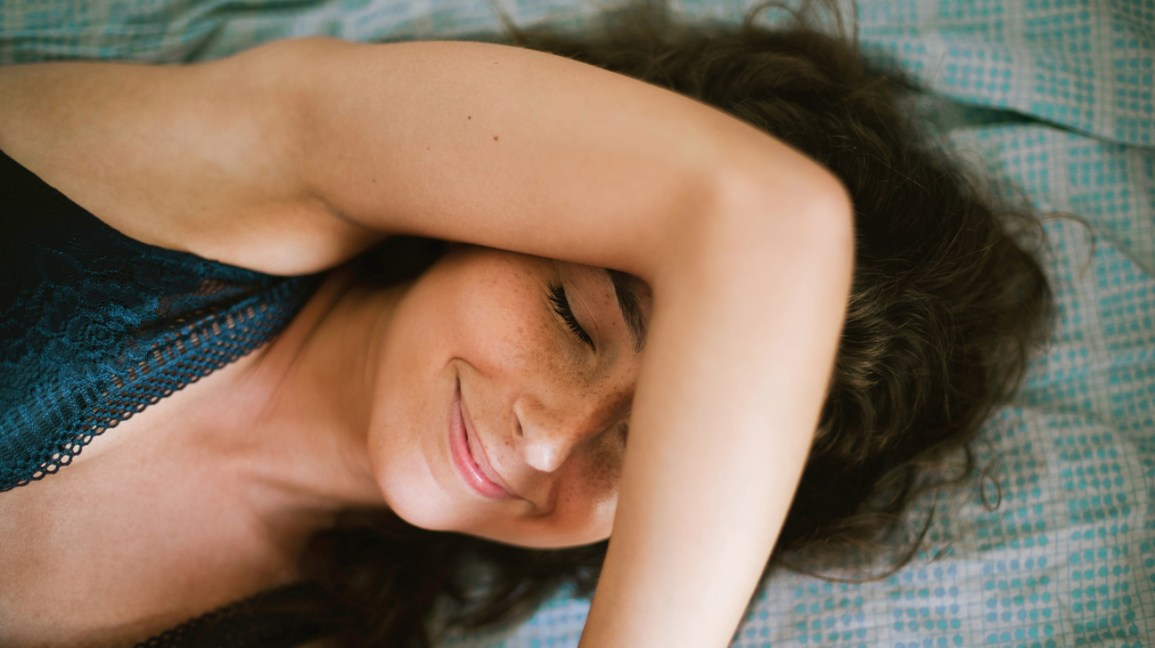 cropped view of a person laying in bed smiling