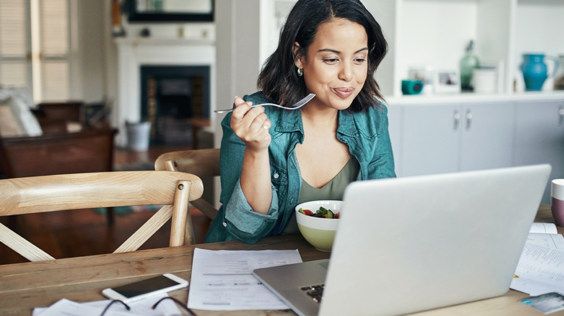 Woman eating while working from home