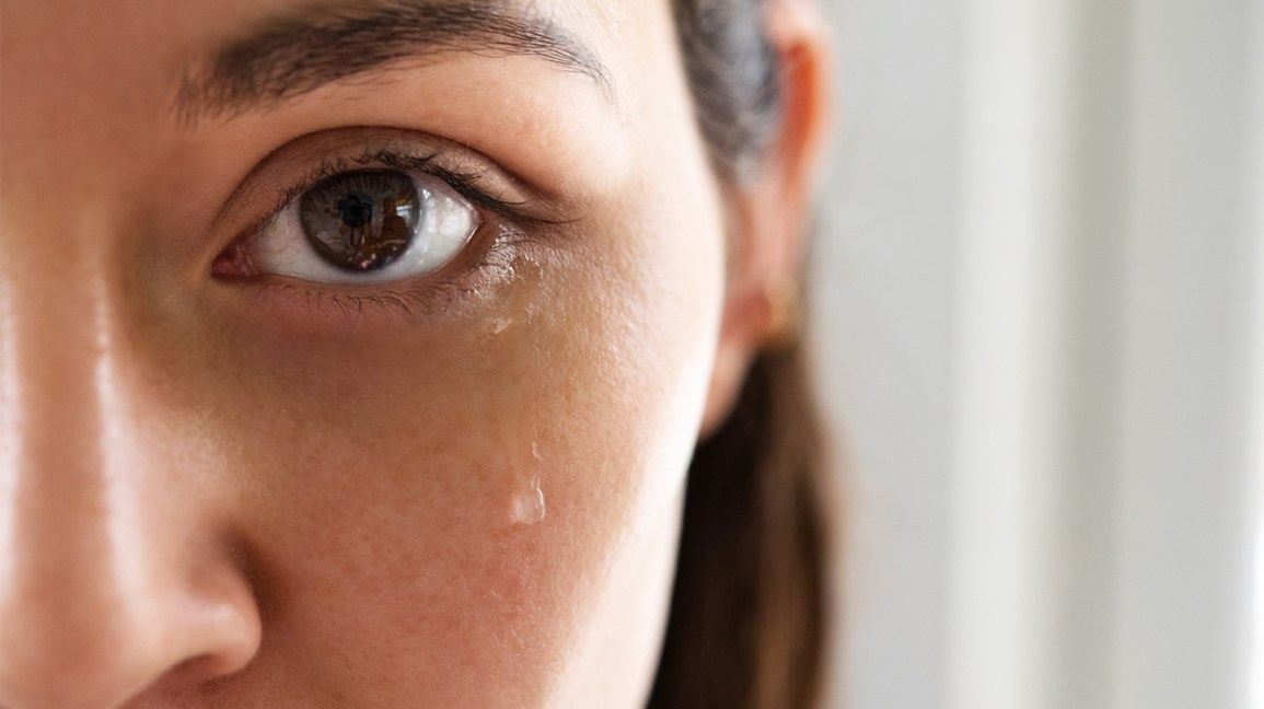 Closeup of half of woman's face crying