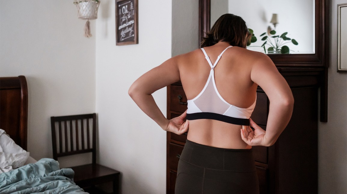 back view of a person wearing a white racerback sports bra and black leggings