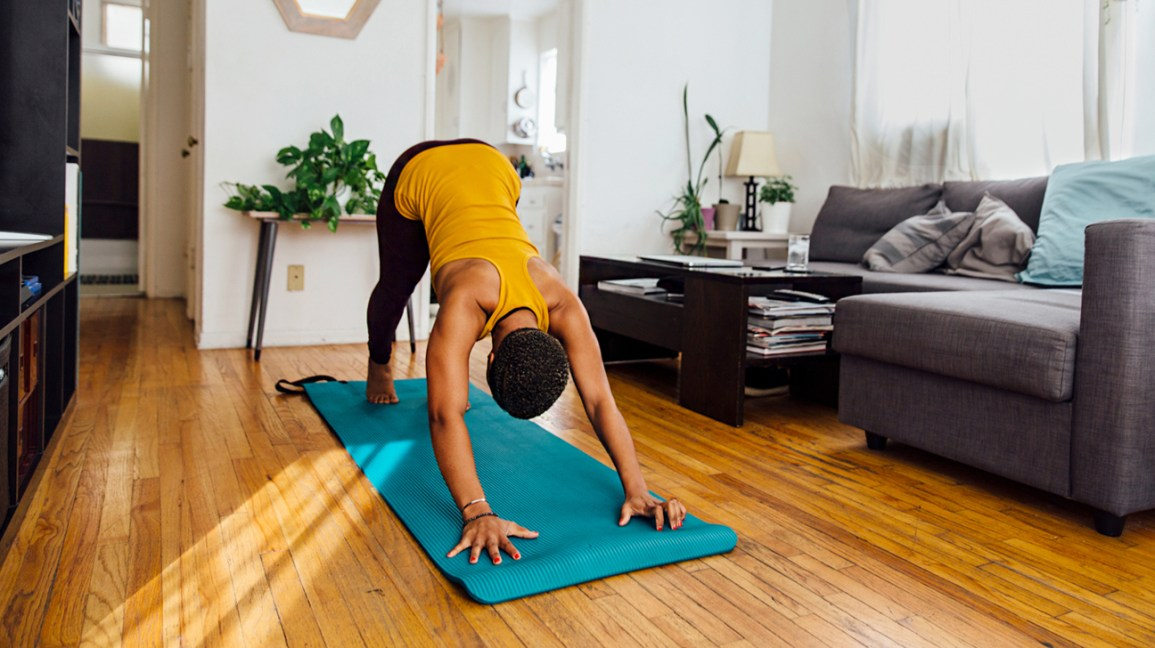 Woman doing yoga in sunny living room