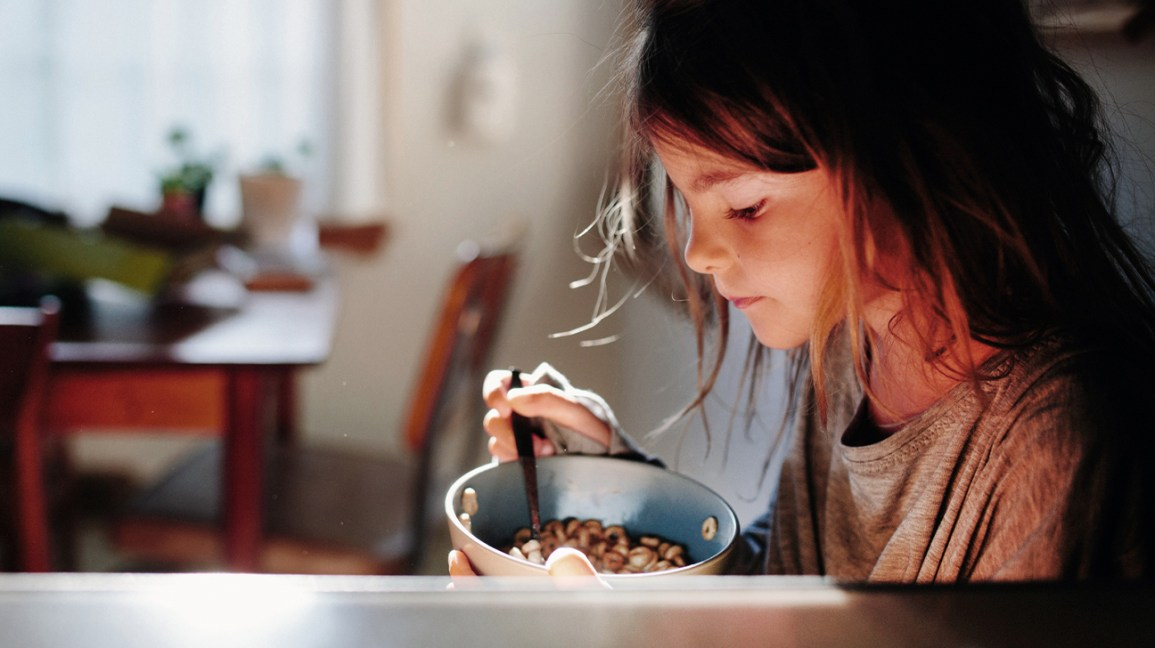young girl with a bowl of Cheerios