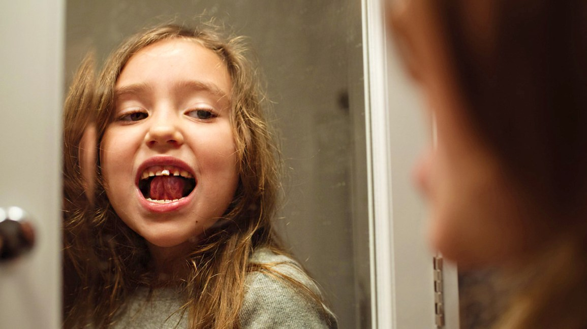 young girl losing baby tooth