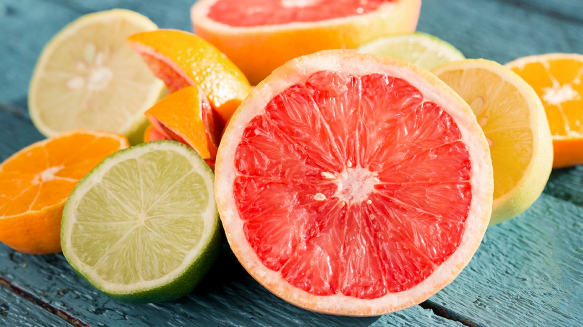 wedges of grapefruit, lime, orange, and lemon on top of a turquoise table