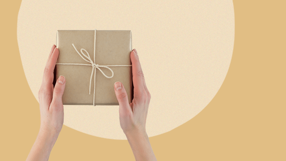 A brown paper package tied up with string on a taupe background