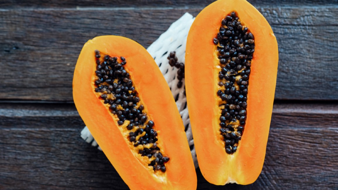 two large papaya halves on a dark wood table