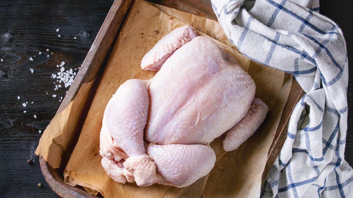 uncooked whole chicken on a metal pan surrounded by salt flakes and a white and blue plaid rag