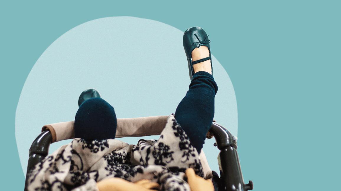 Un bambino che viene spinto in un passeggino su uno sfondo blu e circolare.