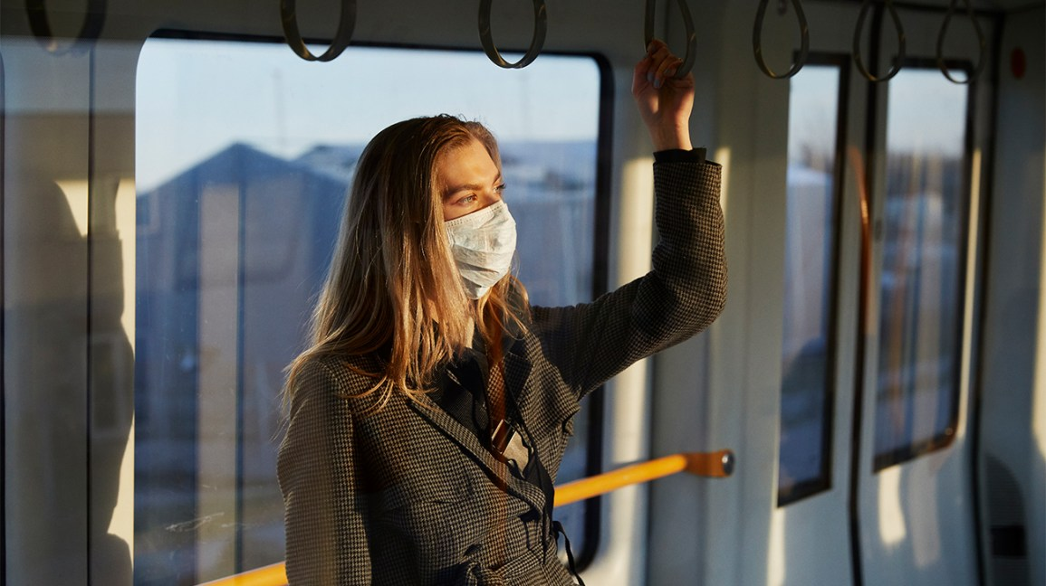 A woman holds onto a rail inside a train, wearing a face mask.