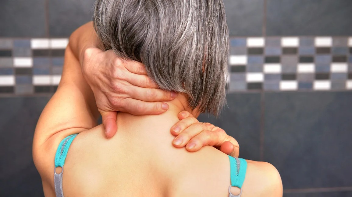 A woman uses her hands to self massage the back of her neck.