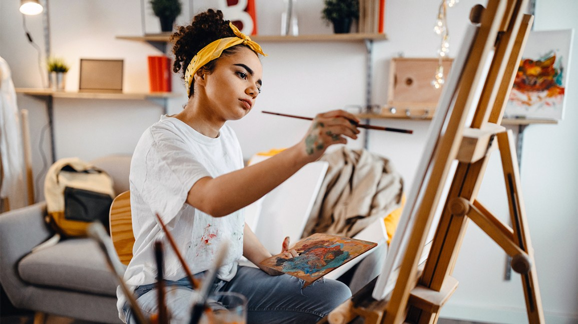 A woman who is forced to stay indoors, holds a paintbrush in her hand while painting a picture on an easel.
