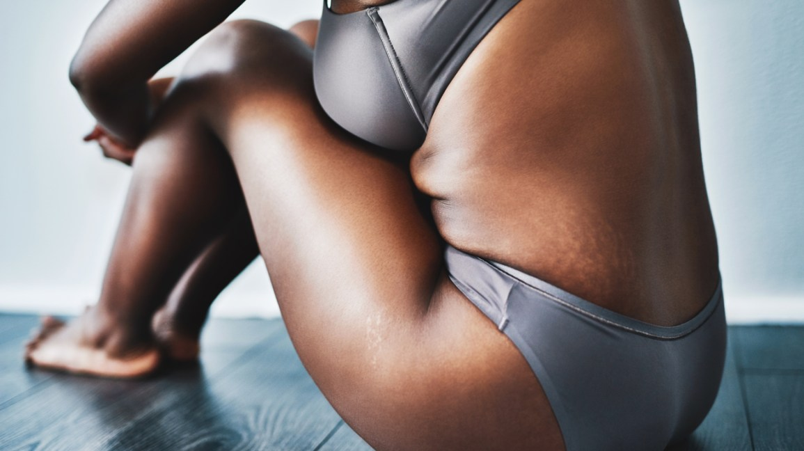 cropped view of a person wearing a heather gray bra and underwear set sitting on a hardwood floor with their knees to their chest