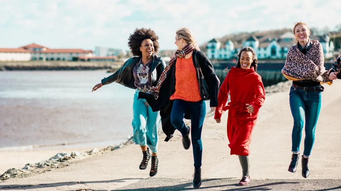 grupo de amigos de mãos dadas pulando na praia