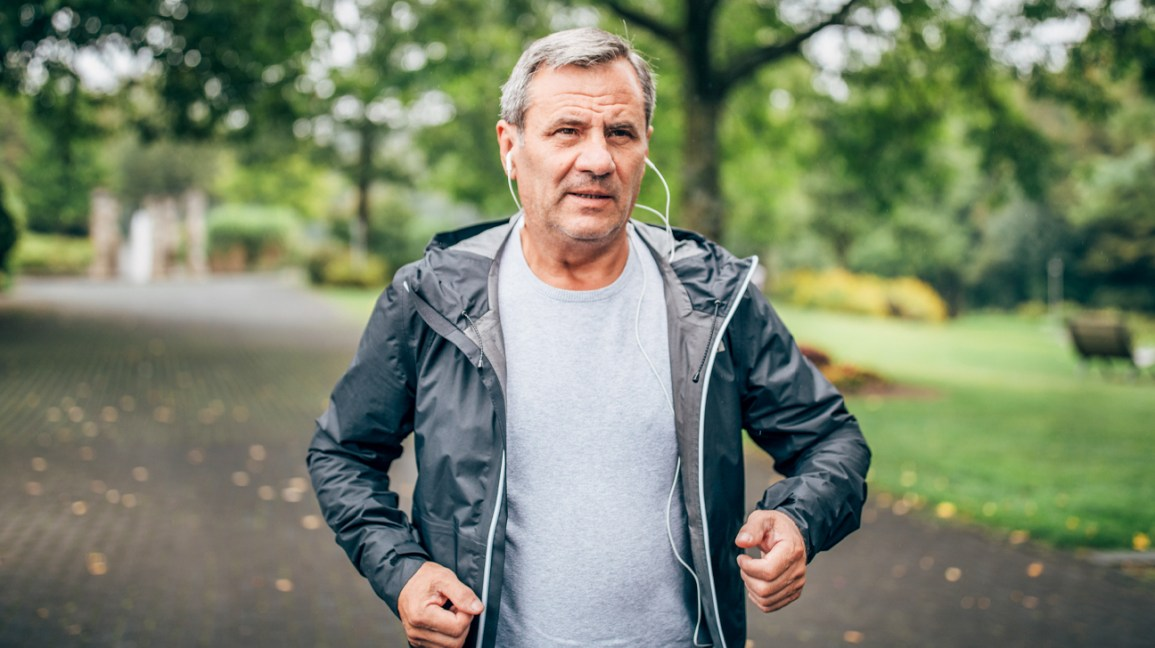 older man jogging gently in park