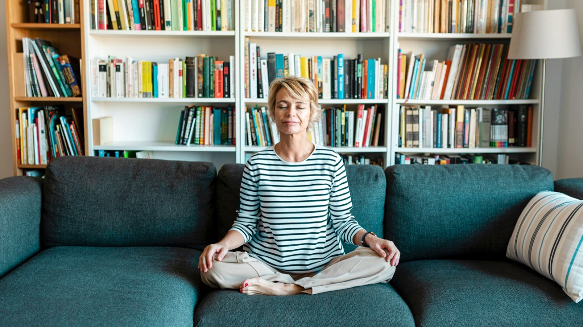 woman meditating on couch at home