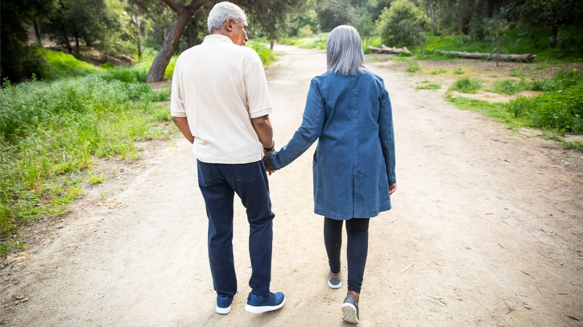 older couple walking outside facing path