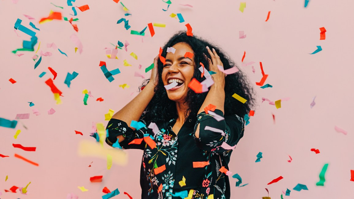 woman standing in front of a pastel pink wall, smiling in excitement as a variety of colored confetti drops from the ceiling