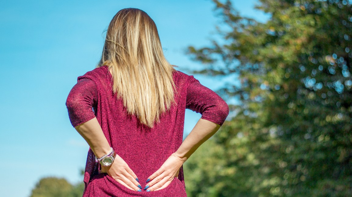 A woman stands outdoors rubbing her lower back where she feels pain.