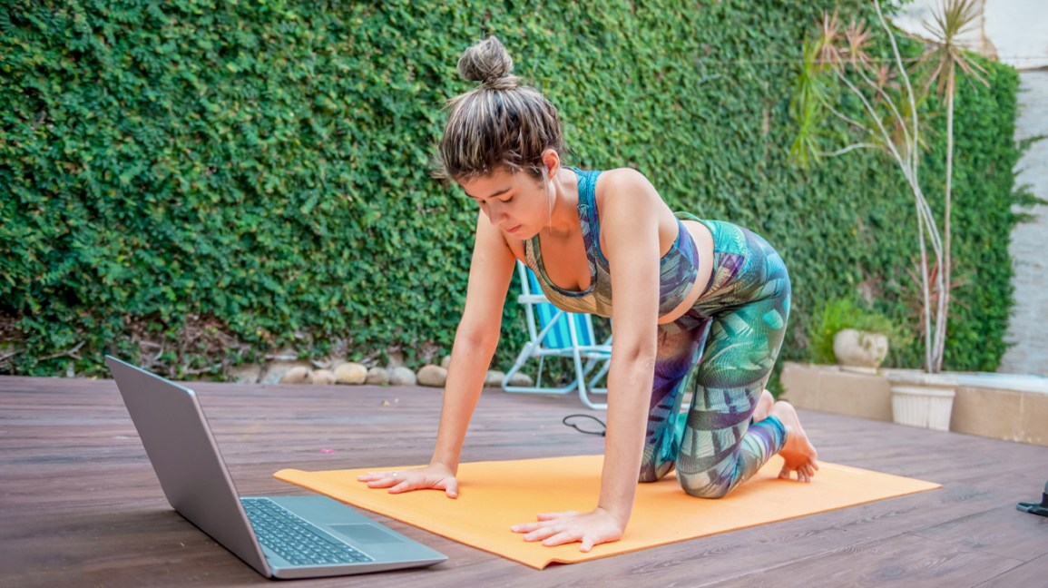 young woman doing yoga outside on her deck, using a laptop