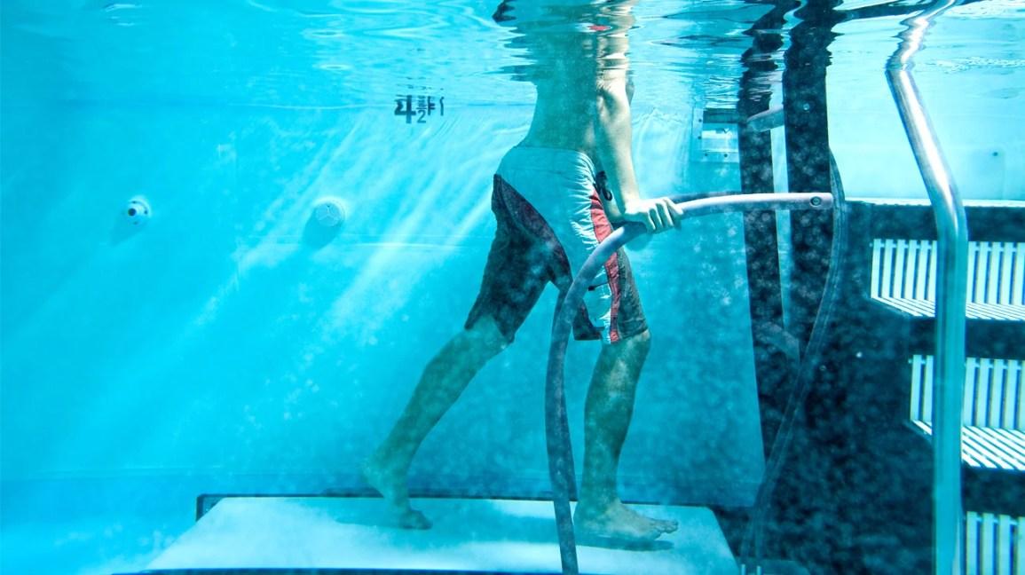 Pemandangan bawah laut dari seorang pria yang mengenakan celana pendek berenang berlari di kolam renang