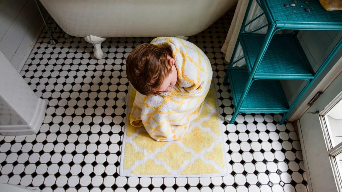 criança infeliz enrolada em uma toalha no chão do banheiro