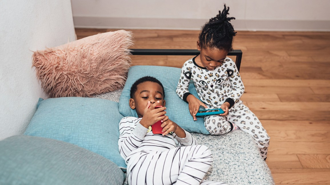 Two kids playing on tablets.