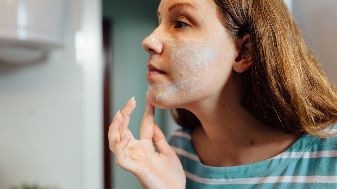 woman applying acne cream to her face